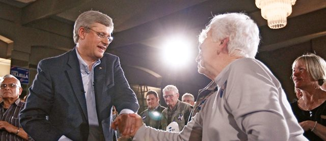Conservative leader and Canada's PM Harper shakes hands with supporter during a campaign rally in St. Catharines
