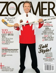 Paul Henderson smiling wearing 1972 Hockey Jersey over a shirt and tie holding a hockey stick in two hands out in front of his chest