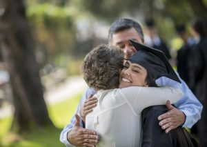 Happy graduation day - family hugging a female student