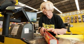 An elderly female employee working at the checkout counter in Jesse & Kelly's No Frills supermarket store Ontario, Canada. Image shot 05/2012. Exact date unknown.