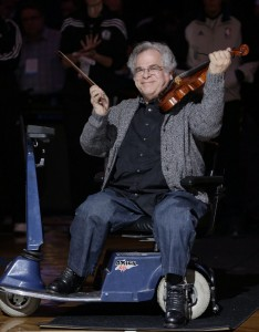 Violinist Itzhak Perlman reacts to the crowd after playing the national anthem before the start of the Brooklyn Nets game against the Orlando Magic in an NBA basketball game at the Barclays Center, Monday, Jan. 28, 2013 in New York. (AP Photo/Kathy Willens)